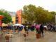 Menschen stehen auf einem Platz. Ihre Blicke sind zu einen Paviilion gerichtet. Sie haben Schirme, da es regnet.